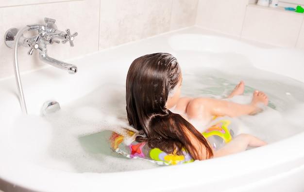 Kleines mädchen der rückansicht badet in einer badewanne mit schaum und mit einem gummiring. konzept zur nervenberuhigung bei kindern und hygienetraining. exemplar