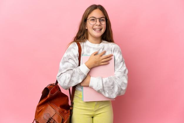 Kleines mädchen der schülerin über isoliertem rosa hintergrund, das viel lächelt