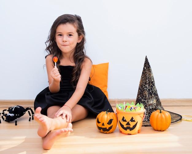 Kleines mädchen der vorderansicht, das auf boden auf halloween sitzt