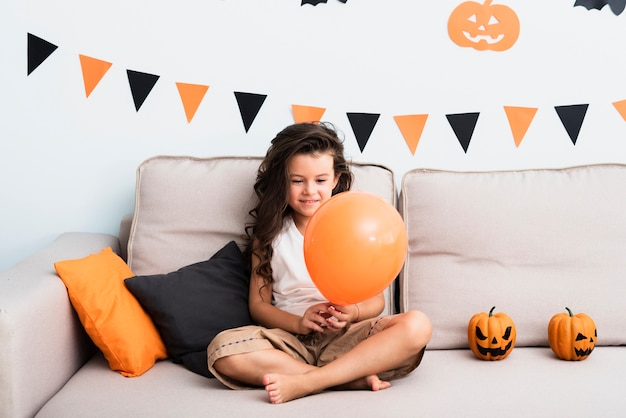 Kleines mädchen der vorderansicht, das einen halloween-ballon hält