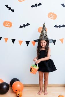 Kleines mädchen der vorderansicht im hexenkostüm für halloween