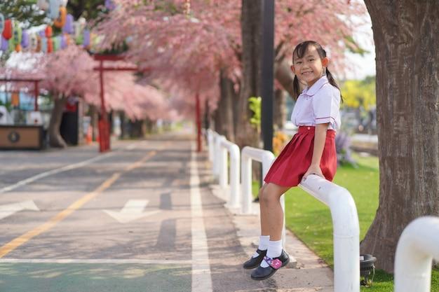Kleines mädchen des glücklichen asiatischen kindergartens im garten unter dem blühenden kirschblüte-baum