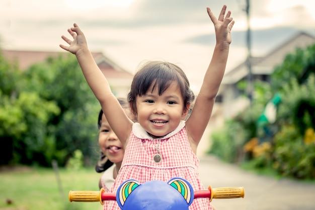 Kleines mädchen des kindes hebt ihre hand an und hat spaß, dreirad mit schwester zu reiten