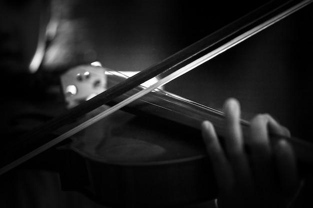 Kleines mädchen des nahaufnahmeschusses, welches das violinenorchester instrumental mit dunkler ton- und lichteffektdunkelheit spielt und korn verarbeitete flache schärfentiefe des ausgewählten fokus