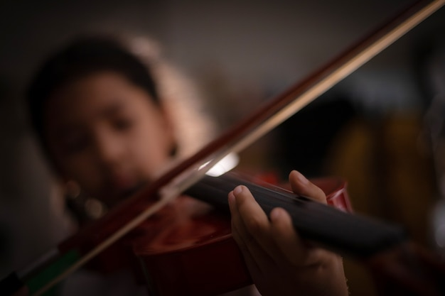 Kleines mädchen des nahaufnahmeschusses, welches das violinenorchester instrumental mit weinleseton und lichteffektdunkelheit spielt und korn verarbeitete flache schärfentiefe des ausgewählten fokus