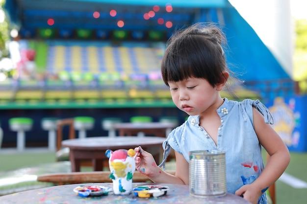 Kleines mädchen des porträts beabsichtigen, auf stuckpuppe zu malen