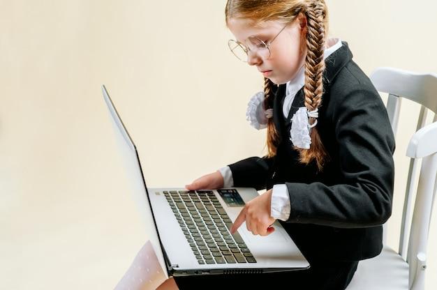 Kleines mädchen des schulpflichtigen alters schaut in einem laptop auf einem hellen hintergrund, internetsucht