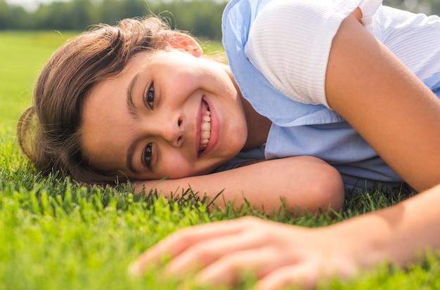 Kleines mädchen des smiley, welches die kamera beim bleiben auf gras betrachtet