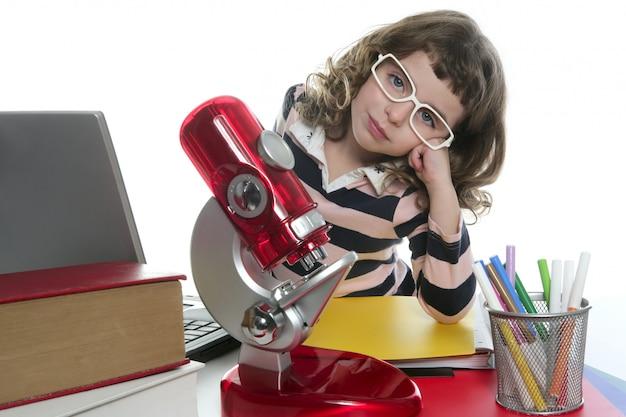 Kleines mädchen des studenten mit mikroskop und laptop