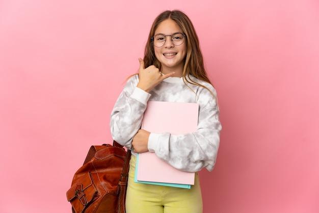 Kleines mädchen des studenten über lokalisiertem rosa hintergrund, der telefongeste macht. ruf mich zurück zeichen