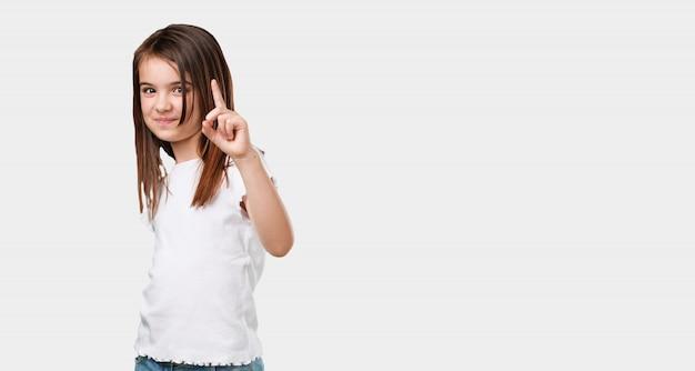 Kleines mädchen des vollen körpers, das nummer eins, symbol der zählung, konzept der mathematik, überzeugt und nett zeigt