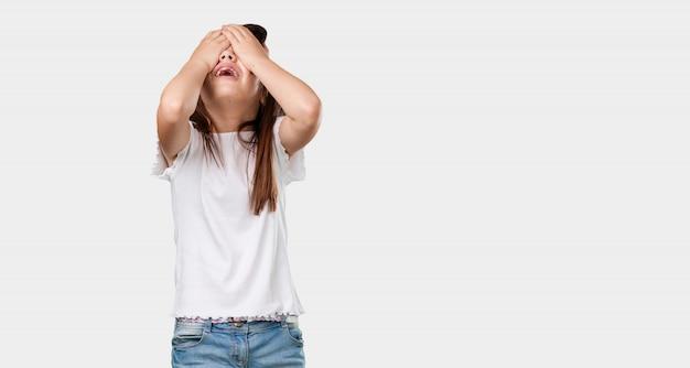 Kleines mädchen des vollen körpers frustriert und verzweifelt, verärgert und traurig mit den händen auf dem kopf