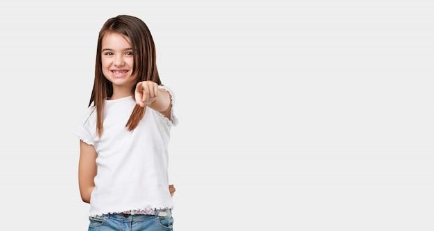 Kleines mädchen des vollen körpers nett und lächeln, zeigend auf die front