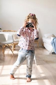 Kleines mädchen des vollen schusses, das fotos mit kamera macht