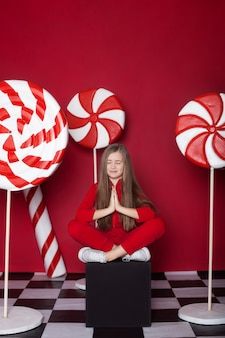 Kleines mädchen entspannen mit riesigen weihnachtsbonbons auf einem roten hintergrund.