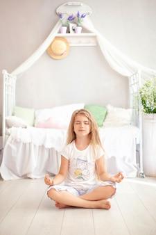 Kleines mädchen entspannen und meditiert in yoga-pose im bett