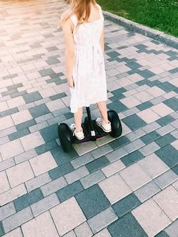 Kleines mädchen fahren auf ein hoverboard im park. rückansicht