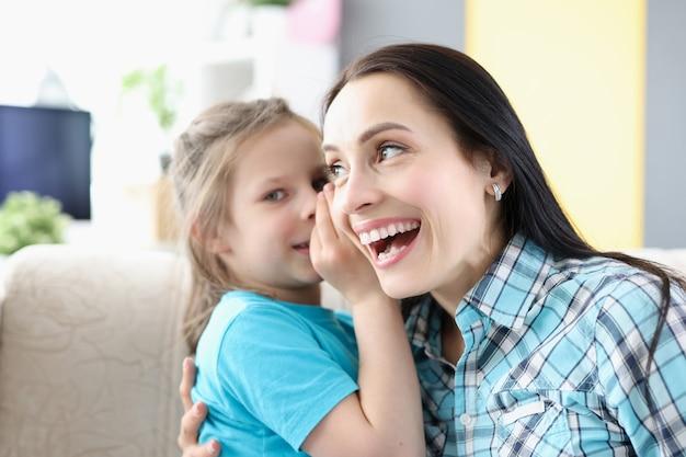 Kleines mädchen flüstert mama zu hause geheimnis ins ohr