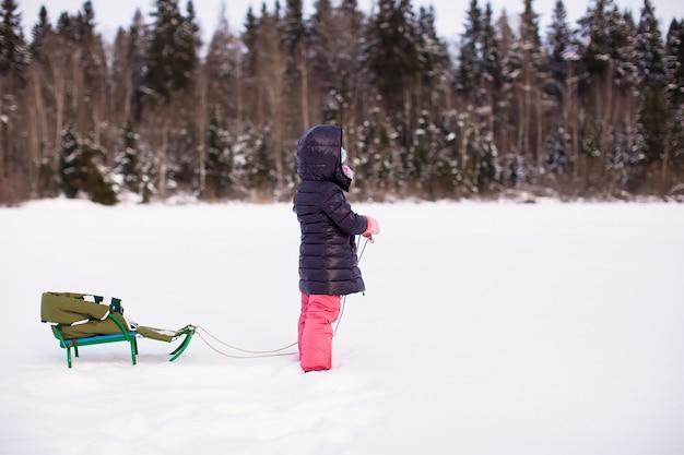Kleines mädchen geht an einem warmen wintertag rodeln