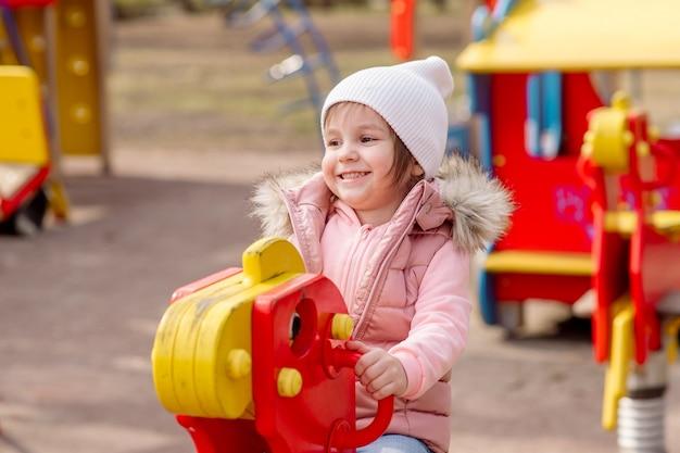 Kleines mädchen geht auf dem spielplatz in der straße im frühjahr