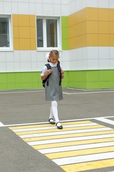 Kleines mädchen geht auf einem fußgängerüberweg zur schule