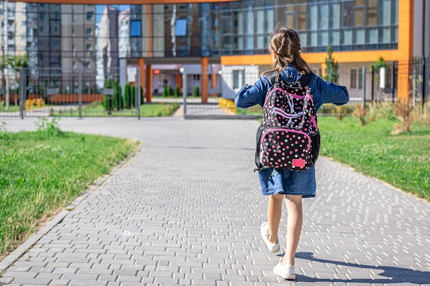 Kleines mädchen geht in die grundschule. kind mit rucksack wird lernen. zurück zum schulkonzept.