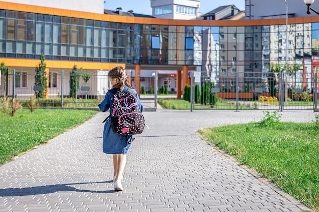 Kleines mädchen geht in die grundschule kind mit rucksack wird lernen