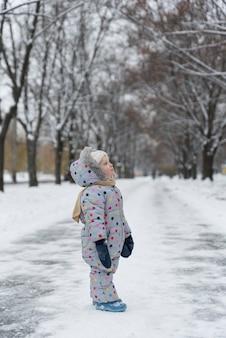 Kleines mädchen geht in winterpark. vertikaler rahmen.