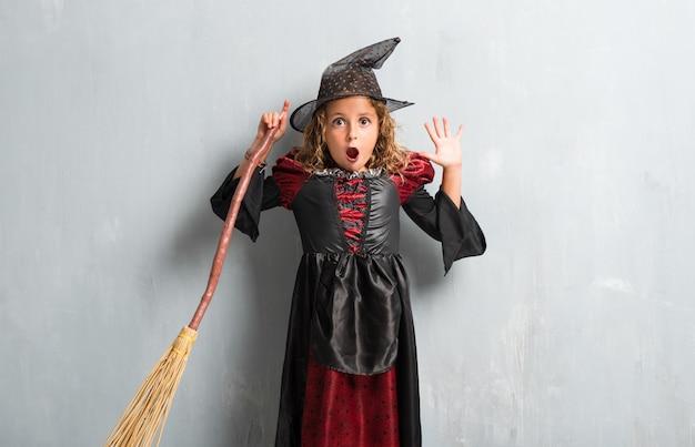 Kleines mädchen gekleidet als hexe für halloween-feiertage, die überraschungsgeste machen