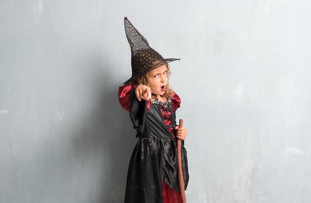 Kleines mädchen gekleidet als hexe für halloween-feiertage und -c $ schreien