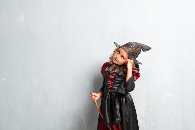 Kleines mädchen gekleidet als hexe für halloween-feiertage und -denken