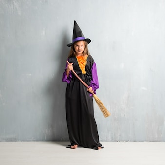 Kleines mädchen gekleidet als hexe für halloween-feiertage und einen besen halten