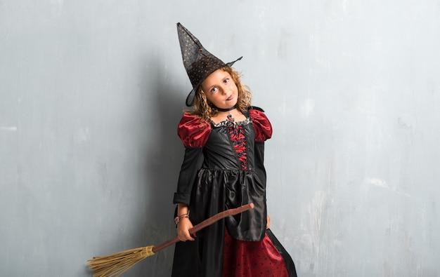 Kleines mädchen gekleidet als hexe für halloween-feiertage und ihre zunge herausnehmen
