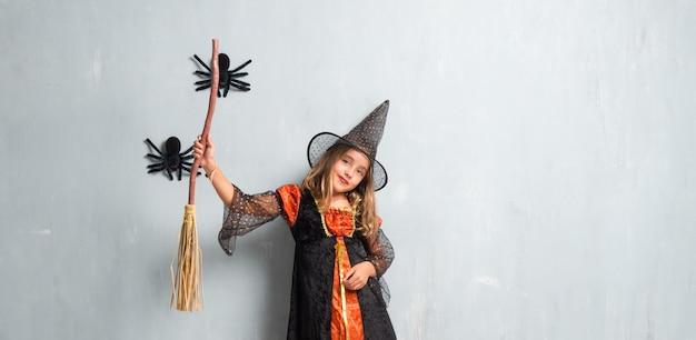 Kleines mädchen gekleidet als hexe für halloween-feiertage