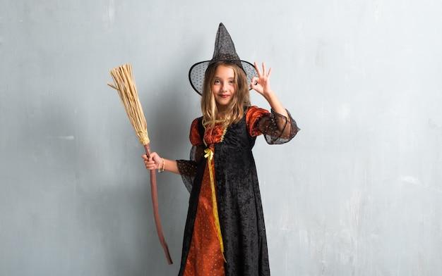Kleines mädchen gekleidet als hexe und einen besen für halloween-feiertage halten, die okayzeichen machen