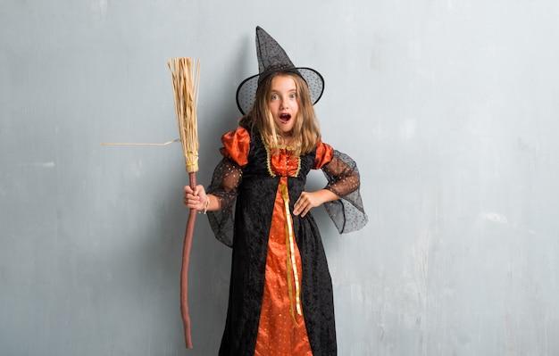 Kleines mädchen gekleidet als hexe und einen besen für halloween-feiertage halten