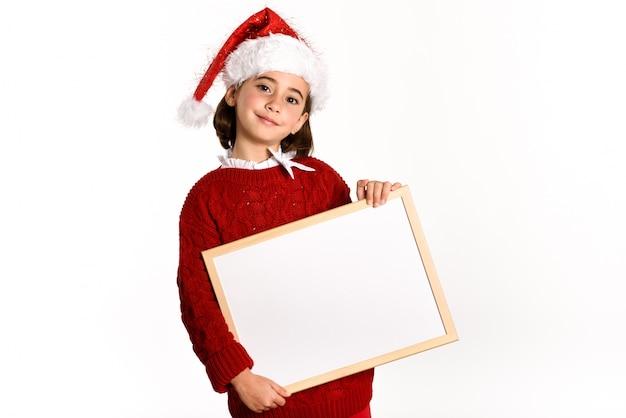 Kleines mädchen gekleidet als weihnachtsmann mit einem weißen brett in einem weißen hintergrund