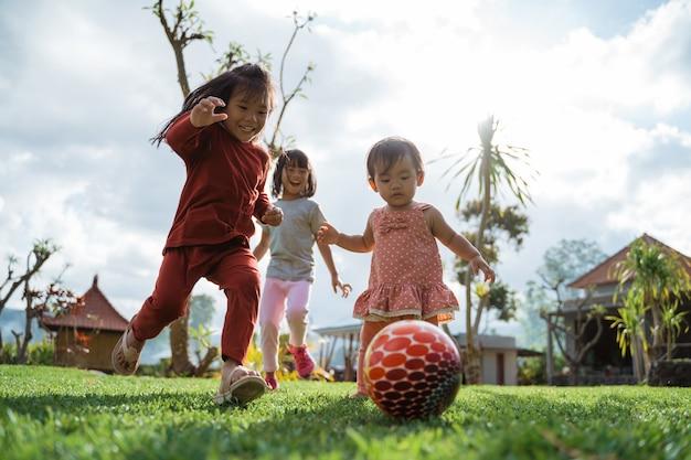 Kleines mädchen genoss es, am sonnigen tag zusammen im hinterhof ball zu spielen
