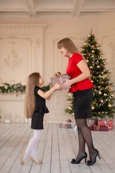 Kleines mädchen gibt ihrer mutter eine schachtel mit einem weihnachtsgeschenk.