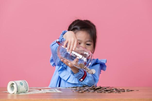 Kleines mädchen gießt die münzen aus einem transparenten glasgefäß heraus