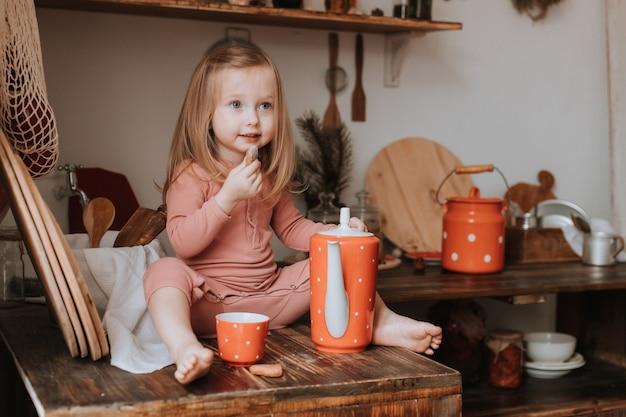 Kleines mädchen gießt tee in eine tasse aus einer teekanne aus rotem keramikgeschirr in einer holzküche mit weißen erbsen