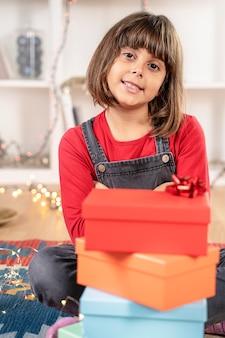 Kleines mädchen glücklich mit weihnachtsgeschenken