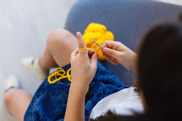 Kleines mädchen häkelt mit gelben fäden. ansicht von oben. dekoration machen.