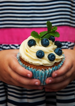 Kleines mädchen hält cupcake