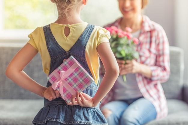 Kleines mädchen hält eine geschenkbox für ihre schöne mutter.