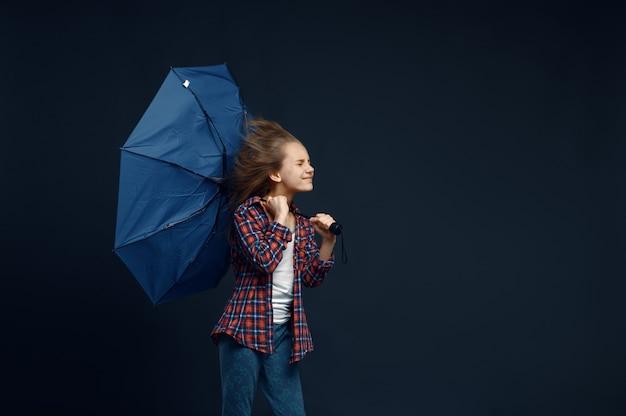 Kleines mädchen hält einen regenschirm, windeffekt, starken luftstrom