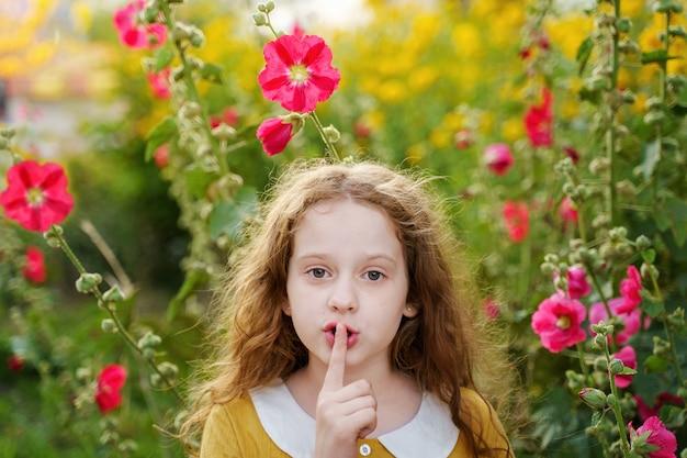 Kleines mädchen hält finger auf lippen bittet um ruhe.