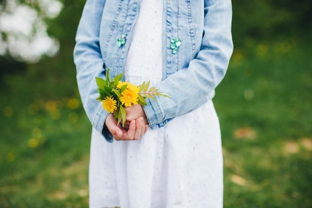 Kleines mädchen hält gelbe kamillenblüten. hochwertiges foto