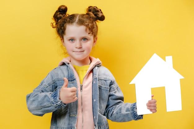 Kleines mädchen hält kleines papierhaus und mit dem daumen nach oben auf gelbem hintergrund isoliert isolated