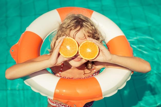 Kleines mädchen hält orangen über den augen mit einem aufblasbaren ring im schwimmbad ring